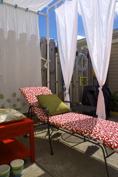Small patio makeover and decoration on a budget. Repainted the side table (from Goodwill) in red. A DIY canopy (8'x7'x8') using PVC pipes with white curtains (muslin fabric). The green pillow is made from old fabric.