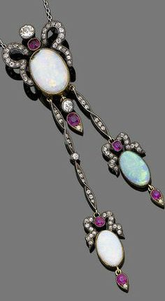 An opal, diamond and ruby negligée necklace The necklace designed as an old brilliant and single-cut diamond and circular-cut ruby scrolling surmount, suspending an oval cabochon opal with circular-cut ruby and single-cut diamond terminal, terminating in two similarly-set pendants, to a trace-link chain, diamonds approx. 1.65ct total, length 54.0cm