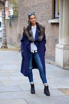 30 Ways to Look Stylish in the Dead of Winter - long navy blue winter coat with fur collar + cuffed skinny jeans and chunky ankle boots