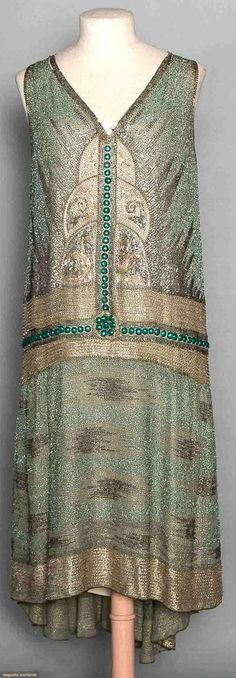 "BEADED GREEN FLAPPER DRESS, LATE 1920s Seafoam green cotton gauze, ground of metallic silver & green embroidered vermicelli w/ designs beaded in silver & gold bugle beads, gold balls & emerald green domed paillettes, B 34"", H 38"", L 41""-47"", (series of small tears under right arm, largest is 0.75"", bead losses) very good."