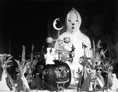 A person in a ghost costume stands with a table full of Halloween decorations in a rural U.S. schoolhouse in 1905.