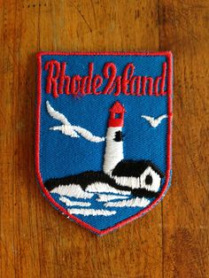Rhode Island Vintage Travel Patch by Voyager    The picture is a lighthouse and a seagull on a blue background.    Its about 2 and 1/2 inches