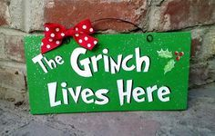 6x12 in. recycled wood sign with print. Coated with indoor/outdoor gloss and clear glitter. Wire and bow accent. The Grinch Lives Here. -------( Production &amp