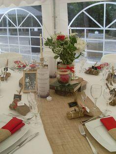 Voici un décor de table champêtre réalisé pour un de nos mariages. La jute apporte vraiment un plus à cette décoration qui – au départ – est dans des tonalités très traditionnelles : rouge, vert, blanc. L'ensemble apparait comme raffiné, très naturel et chaleureux. FacebookEmail