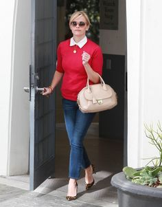 Reese Witherspoon in a super cute red sweater, jeans and leopard pumps