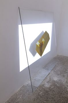 ŁUKASZ JASTURBCZAK Hologram, 2013, installation, glass, golden spray, HD projection, 100 x 100 cm