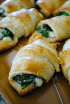 The perfect appetizer or snack! Enjoy :)  Cheesy Spinach Crescent Rolls Ingredients: 2 tubes Pillsbury Cheesy Spinach Crescent Rolls  (8 ct. each), 4 oz. crumbled feta cheese, 4 oz. shredded mozzarella cheese *feel free to use an type of cheese(s) that are your favorite, 3 oz. fresh baby spinach, chopped (about half of a pre-washed bag), 1 egg white, beaten, 1/4 tsp. red pepper flakes, dash of salt and pepper