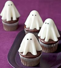 Ghost cupcakes made with white fondant draped over suckers. Cute!