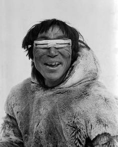 Smiling Inuit man wearing bone snow goggles.