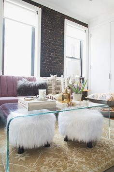 """I love how we were able to pack SO MUCH into her classic"""" (AKA small) New York apartment."""" The glass coffee table is functional and keeps the space feeling airy."""