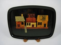 Couroc of Monterey, California produced this black tray with the inlaid design of a fishing village with a brass ladder leading to the water and a brass fish on the roof of one of the buildings.  The marquetry is done with woods and brass on this tray design that was hand inlaid by craftsmen.  Measures 12.5 long and 9.5 wide. Rectangular in form with curved edges. The label on the bottom reads COUROC IS UNIQUE. This also states that Couroc serving pieces are cherished gifts because of the…