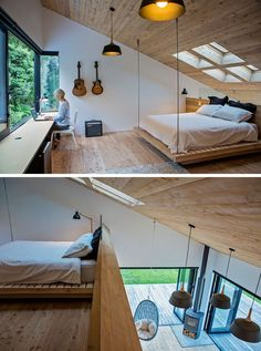 The mezzanine in this modern house is home to a bedroom. Four skylights are positioned above the bed, which is partially suspended from the sloped ceiling. From behind the bed you can see the living room below. #Mezzanine #ModernBedroom #Skylights #ModernInteriorDesign