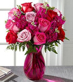 FTD Pure Romance Rose Bouquet - PREMIUM | Utterly romantic and blossoming with your love through every blushing bloom, this gorgeous rose bouquet is out to convey your hearts every wish. Hot pink, red, and lavender roses mingle with fragrant fuchsia gilly flowers, beautifully accented with lush greens while seated in a vibrant pink glass vase. The perfect anniversary, I love you, or Valentines Day gift!