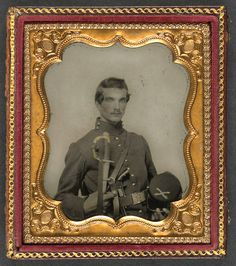 Unidentified soldier in Union uniform holding kepi with cavalry insignia, cavalry saber, and Smith and Wesson revolver. c. 1861.
