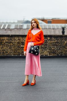 My blogger pal Hannah Farrington of Hannah Louise Fashion looking very ladylike at LFW in a pink pleated skirt and clashing red v-neck jumper with a star print bag. Colour blocking goals right there.