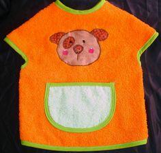 Alegre babero delantal en tela de rizo color naranja con bolsillo en color fucsia, ribeteado con cinta al bies color verde manzana. Clic en la imagen para seguir leyendo.