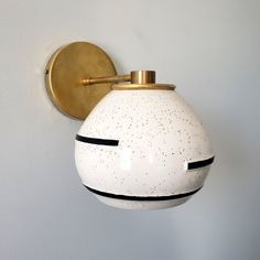 Terazzo inspired boho style wall sconce with a handmade ceramic shade that features light speckling and modern geometric black lines. Perfect for a number of different decor styles. Unique and made in New Orleans. Modern Interior Decor, Travel Inspired Decor, Feature Light, Light, Modern Lighting Design, Mid Century Modern Interiors, Sconces, Brass Accents, Bulb