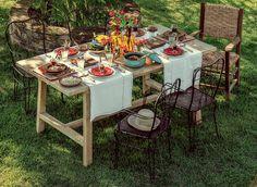 Caminhos de mesa e tábuas usadas como jogo americano substituem a toalha neste almoço no campo. No centro, as garrafas fazem o papel dos vasos para as flores. Produção de Ana Cláudia Marques e Ellen Annora