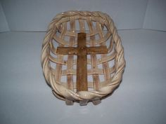 Hand crafted woven ceramic bread basket with christian cross design in center. When you bake your bread or rolls in this bowl, it will take on the