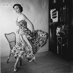 ca. 1954 --- Model wearing floral dress with sash by Schiaparelli.