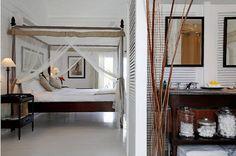 Dark furniture with white walls & floor. Very Caribbean island feeling.