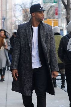 Pairing a charcoal overcoat with black chinos is an on-point option for a day in the office.   Shop this look on Lookastic: https://lookastic.com/men/looks/overcoat-bomber-jacket-crew-neck-t-shirt/16500   — Black Baseball Cap  — White Crew-neck T-shirt  — Black Bomber Jacket  — Charcoal Overcoat  — Black Chinos