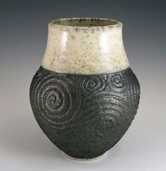 This raku vase has been formed on the potter's wheel, skillfully carved with a free-form spiral design, glazed, then fired using an American variation of the Japanese technique of raku