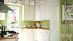 Perinteisen tyylinen vihreä keittiö, jossa valkoiset kaapit