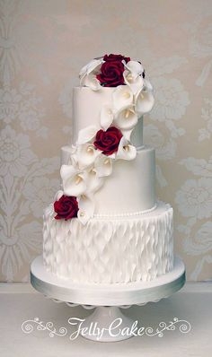 A pretty cascade of sugar calla lilies and deep red roses, to match the wedding flowers, cascading down the front of the top two tiers. The bottom tier decorated with vertical ruffles. Delivered to the gorgeous The Manor House, an Exclusive Hotel & Golf Club at Castle Combe.