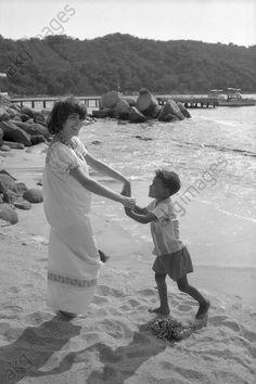 Mireille Mathieu lors d'une tournée au Brésil en novembre 1972 : la chanteuse tient par les mains un petit Brésilien et danse avec lui sur la plage