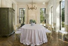 Euro style dining room. Interior design by MILIEU editor Pamela Pierce (French, Swedish, Belgian, European, Gustavian, Scandinavian antiques, modern art, minimal, feminine, romantic, timeless, tranquil, farmhouse, elegant, traditional decor with reclaimed stone, biots, white roses, linen, slipcovers, ruffles, skirted tables, Lefroy Brooks, cremone bolts, steel windows and doors, rustic wood, white, neutrals, country, Chateau Domingue, oversize sconces, and chandeliers.