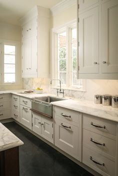 Christopher Olexy - Incredible kitchen with white flush front cabinetry accented with polished nickel handles alongside Calacatta Marble counters and backsplash which highlights a stainless steel apron front sink with bridge faucet over Belgian Blue Star tiled floors.