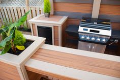 """Backlit stone privacy panels make a cool backdrop for the BBQ, and the dry bar opposite is a handy place for serving food! From """"Decked Out"""" project """"The Waterfall Deck"""".  Deck Design by Paul Lafrance Design."""