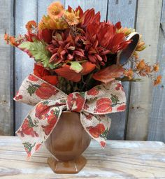 Lovely Fall floral arrangement.  Bouquet of orange sunflowers and yellow mums in old Frankoma vase with burlap ribbon.