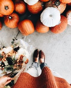 fall or autumn pumpkins with flowers, orange sweater, jeans, and loafers