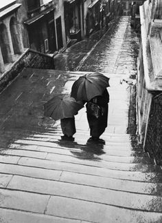 A mother and child walking up a Bristol street in the rain, UK, 1954. © Joseph McKeown