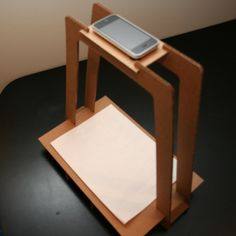 The iPhone Document Scanner can be built using the DIY instructions on this website (you can buy a pre-made one from the website, too).  Maybe this design can be modded to hold an iPad.