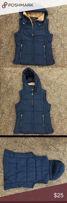 Navy & Gold Puffer Vest with Faux Fur lined Hood Navy Blue Puffer Vest with hood and gold zippers. The hood is NOT removable. Full front zipper closure jacket is fully lined and padded material for warmth and cozy feelings. There is also a button to close neck line together or undone Two zip front zipper pockets. The vest made with 100% polyester. Faux fur-lined neck with hood. This puffer vest woman is machine washable. Do not uses bleach, no iron, and tumble dry medium this vest. Super…