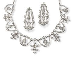 A diamond necklace & pair of earrings, circa 1830.  The necklace designed as a chain of diamonds, suspending at the front a fringe of diamond drops within diamond swags, alternating with stylised anthemion motifs set with similarly cut diamonds, the articulated pendent earrings of highly stylised floral & scroll design set throughout with cushion-shaped & old brilliant-cut diamonds, necklace probably composite, necklace & earrings both mounted in silver & gold