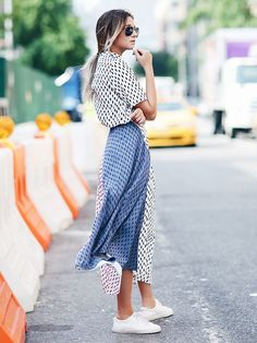 Danielle Bernstein of We Wore What wears a patterned midi dress with easy white sneakers and aviators