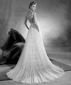 EITANA - A dazzling, sleeveless wedding dress with a bateau neckline and an A-line that flatters the silhouette. A romantic design created in tulle and Chantilly, with suggestive layering on the skirt. A wonderful neckline with gemstones. Doubtlessly the master touch!