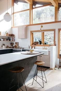 modern malibu hills kitchen with marble island and wood with wrought iron stools. / sfgirlbybay