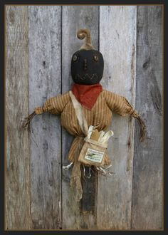 This scarecrow hanger is made from muslin and homespun, mounted on a wood board . He is a sweet door hanger! His head is a pumpkin, and he carries a bag of corn. Finished he is approx. 28-30 inches depending on the board you use. #primitive #scarecrow #pattern #ad