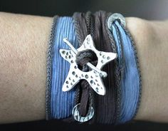 Beautiful swimming starfish adorn this exquisitely hand crafted fine silver toggle. This seaside silver toggle, made from recycled silver, is interlaced with a hand dyed silk ribbon with hues of blue and brown that wraps end over end around your wrist.  The gentle sari textile wrap with cool hues reminiscent of the sea is generous, and flowing in grace and comfort.  The finely crafted artisan toggle is made from pure, fine, enviro-friendly, silver and is 99% pure, created by hand, naturally…