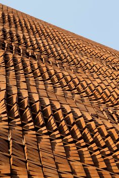 """Close-up of the facade of a building in Tehran, Iran, designed by Admun Design & Construction Studio - photo by Parham Taghioff, via Divisare; """"Rotating the bricks provided the opportunity to have various degrees of openings and the rotation angles are precisely adjusted. ... Despite the complex form of the facade the construction process was easily executable by workers through simple instructions prepared by employing a system of coding."""""""