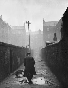 31st January 1948: A man walking through a backstreet in the run-down Gorbals area of Glasgow.