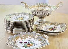 A Ridgway gray-ground part dessert service circa 1830-35 each piece painted in the center with an arrangment of fruit or flowers within the gilt scroll- and floral-molded rim, comprising: a footed reticulated basket, two diamond-shaped two-handled dishes, two square two-handled dishes and twelve plates,