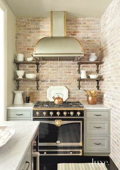 To give the kitchen a loft-like feel, faux brick was added and then distressed to create an aged look. The La Cornue range is paired with a custom hood from Rangecraft, designed by Jenny Wolf Interiors. The shelves, made of reclaimed wood with antique brackets, were also custom-designed.