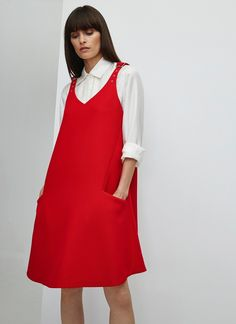 Vestido tipo pichi en color rojo amapola, prenda clave de esta temporada. Escote en V, tirantes con hebillas ajustables y sutil pliegue en la parte trasera. Combínalo con una camisa o jersey para renovar esta tendencia de los años 90.