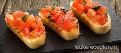krokant geroosterd brood met met een topping van tomaat en basilicum